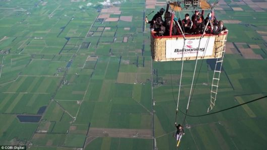 Woman Performs On A Trapeze Attached To A Hot Air Balloon